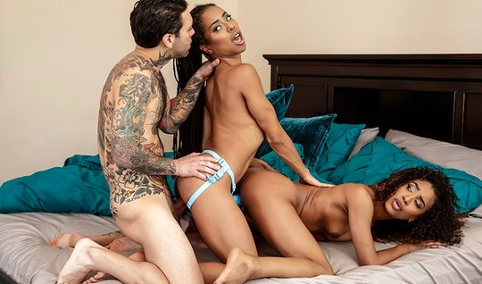 Two sexy ebony pleasing each other with a strap-on and guy with their ...