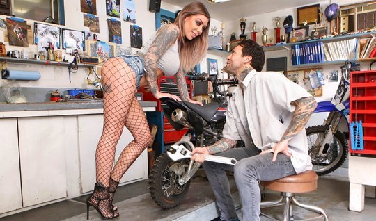 Busty tattooed biker girl caresses the mechanic's hefty cock